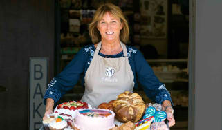 Bakery owner Theresa Hammons in front of her shop holding a collection of her baked goods.