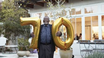 A man holding balloons for his 70th birthday