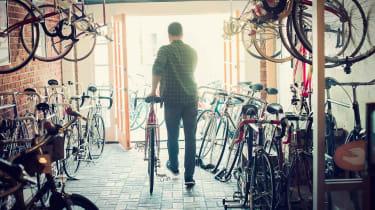 Bike shop owner rolls a bike out the door