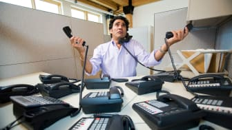 picture of man at work answering multiple phones