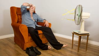 A sweating senior man sits in his easy chair with a fan pointed at hime