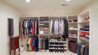 An organized man's walk-in closet filled with clothing