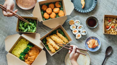 Two people's hands using chopsticks while sharing Asian food takeout.