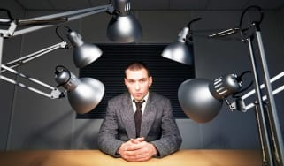 A man sits under interrogation lights.