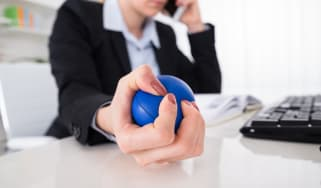 Young Businesswoman Pressing Stressball While Talking On Mobile Phone At Desk