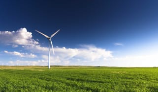 A lone windmill sits on a grassy plain