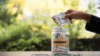 picture of person putting money in a jar for an emergency fund