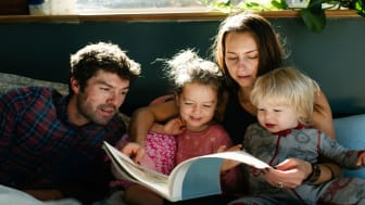 picture of parents reading to their two young children