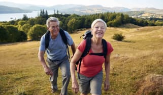 A pair of senior citizens hikes in the foothills of the mountains