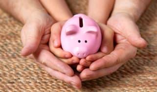 A parent's hands cradle a child's hands holding a piggy bank.