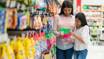 mother and daughter looking at a product at supermarket both smiling