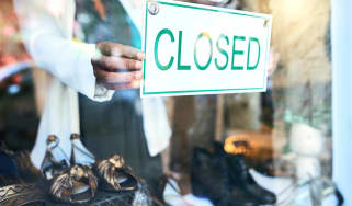 Cropped shot of an unrecognizable woman holding up a closed sign