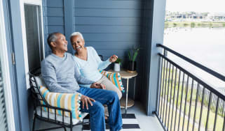 Senior couple sitting on the porch of their Florida retirement home