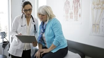 Female doctor and senior patient reviewing medical chart in clinic examination room