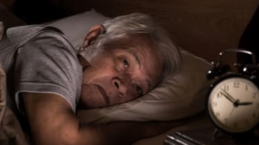 A man lays in bed while having trouble sleeping.