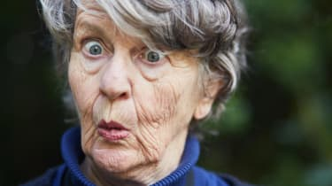 A retired woman has a surprised look on her face.
