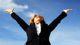 A woman in a business suit jumps for joy.
