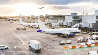 Busy airport view with airplanes and service vehicles at sunset. London airport with aircrafts at gates and taking off, trucks all around and sun setting on background. Travel and industry co