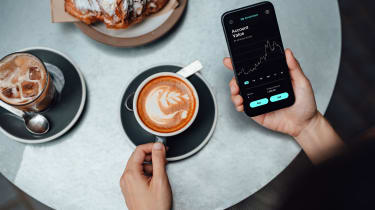 Woman looking at her investing app on phone will drinking morning latte