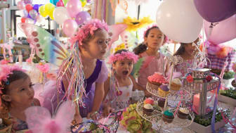 A young girl blows out a candle on a cupcake, at a princess costume themed birthday party.