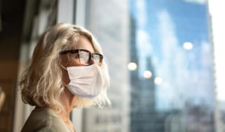 A woman in a business suit wearing a mask looks out an office window.