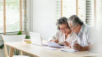 Senior man and woman looking at account book, bill, passbook, receipt and laptop computer on table