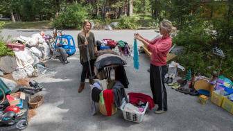 Women look over belongings at garage sale, driveway