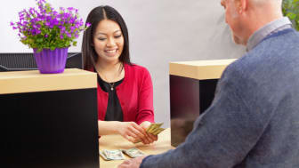 An adult man bank customer making a financial transaction with a bank teller over the counter in a retail bank. The woman Asian bank teller is smiling and cheerfully providing the customer se