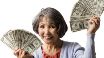 senior woman with hands full of dollars