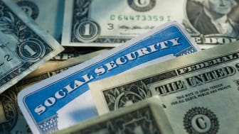 Dollar bills surround a Social Security card