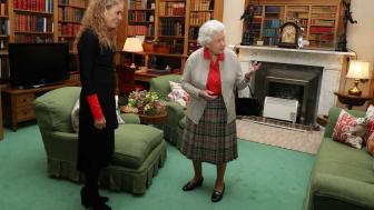 Queen Elizabeth stands in a living quarters near a space heater