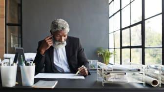 Older man sitting at a desk going through books