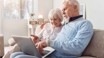 A couple looks at a laptop.