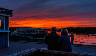 Retired couple sitting in downtown Bar Harbor, Maine in summer during bright red sunset at twilight.