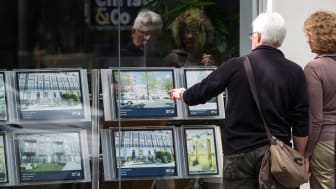 picture of couple looking at pictures of apartment buildings in a real estate office window