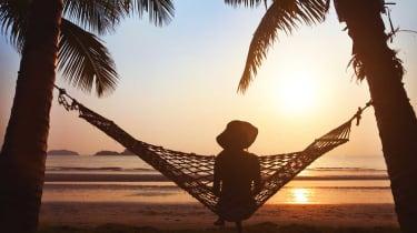 A woman sitting in a hammock on the beach