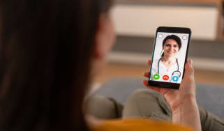 A person holding a phone during a telehealth meeting