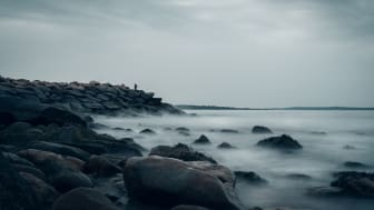 A man fishing while the waves lapping against the rocks of Narragansett, Rhode Island.