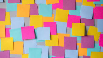 many colorful sticky notes on board background.