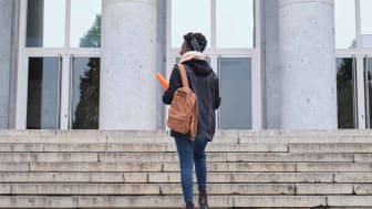 Photo of woman walking up steps to college building