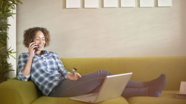 a woman sits on a sofa with her laptop and credit card and chats on the phone
