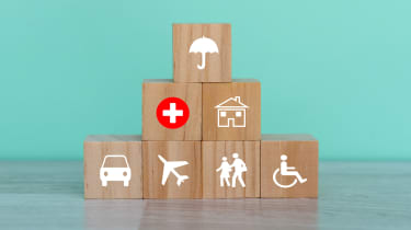 Wooden building blocks with an umbrella, wheelchair and car symbols on them.