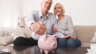 picture of retired couple putting money in a piggy bank