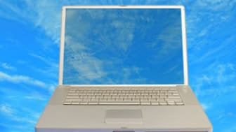 front view of laptop computer with clear screen to blue cloudy background