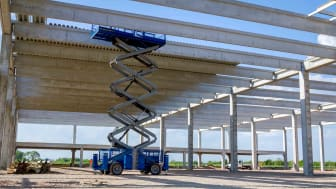 A scissor lift being used during construction of an elevated roadway
