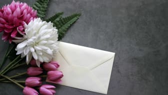 A bouquet of flowers with a white envelope attached.
