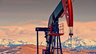 Oil and gas pump jack against mountains, at dusk. Lots of copy space. (Please see my portfolio for related photos and video clips).
