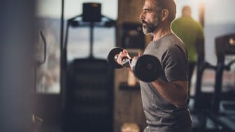 Determined mature man exercising with barbell in a health club.