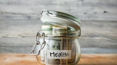 Dollar bills in glass jar isolated on wooden background. Saving money for health.