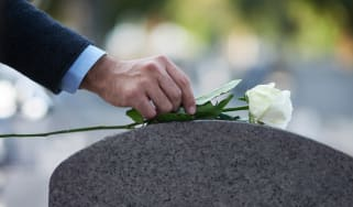Cropped shot of a man placing a white rose on a grave